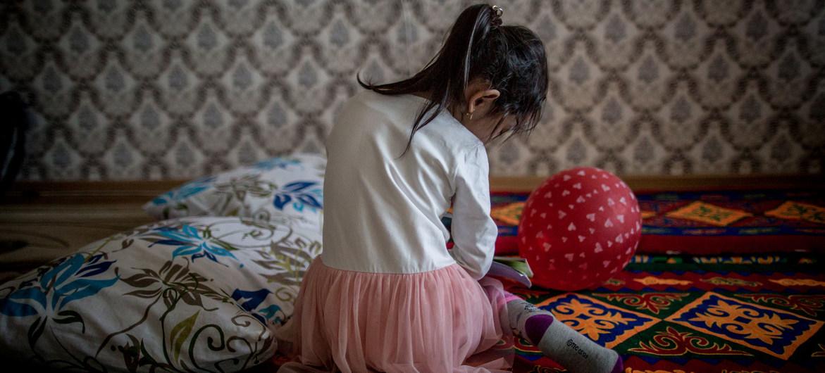 UNICEF/Anush Babajanyan Una niña de cinco años juega en el piso de su familia en Kazajastán, donde UNICEF trabaja para eliminar la violencia doméstica contra los niños.