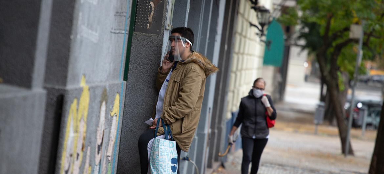 Un hombre habla por teléfono usando una pantalla para protegerse del COVID-19 en Buenos Aires, Argentina.