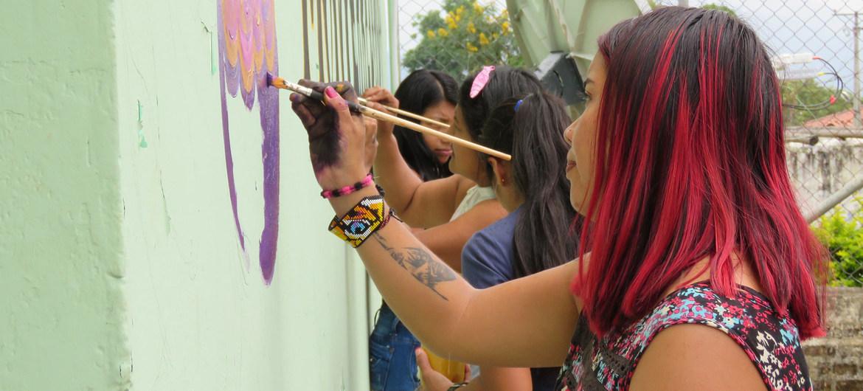 Mujeres colombianas decoran un muro con mensajes de paz.