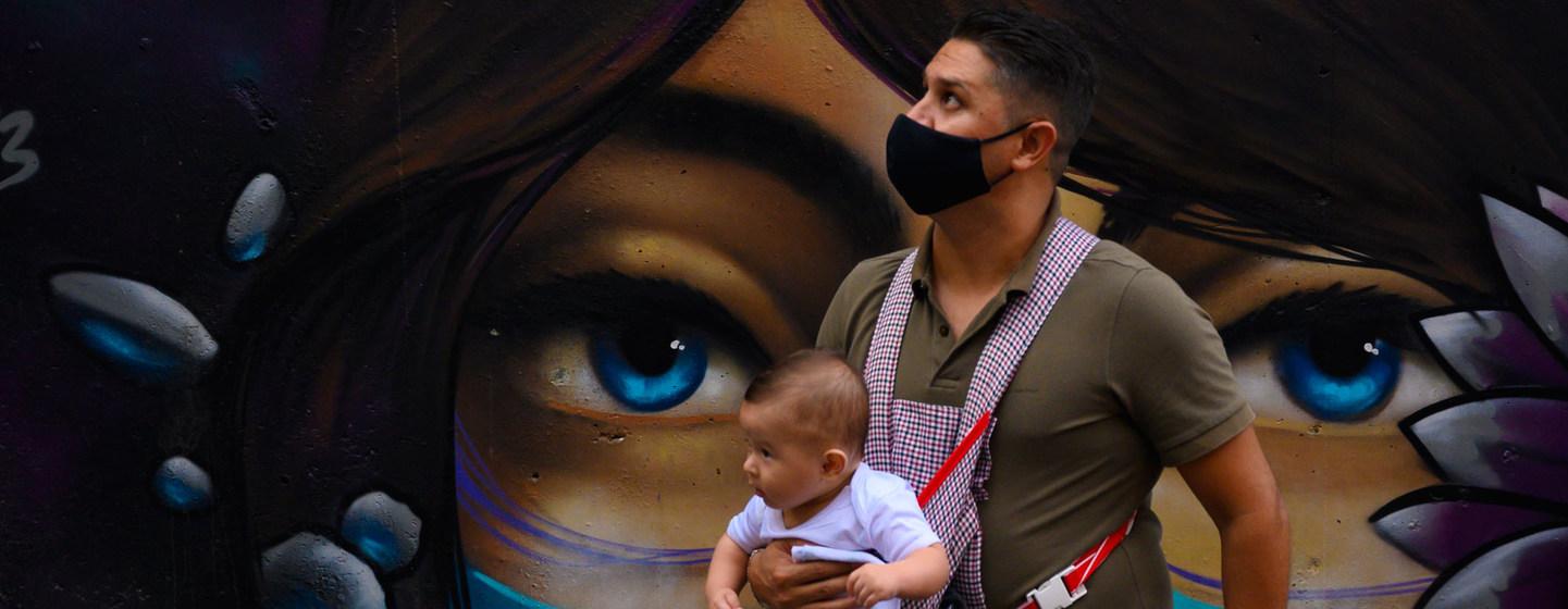 IMF/Joaquin Sarmiento Un padre con su hijo durante la pandemia COVID en la comuna 13 de Medellin, en Colombia.