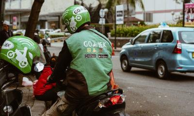 Unsplash/Afif Kusuma Un motociclista de una empresa indonesia de transporte espera a un pasajero.