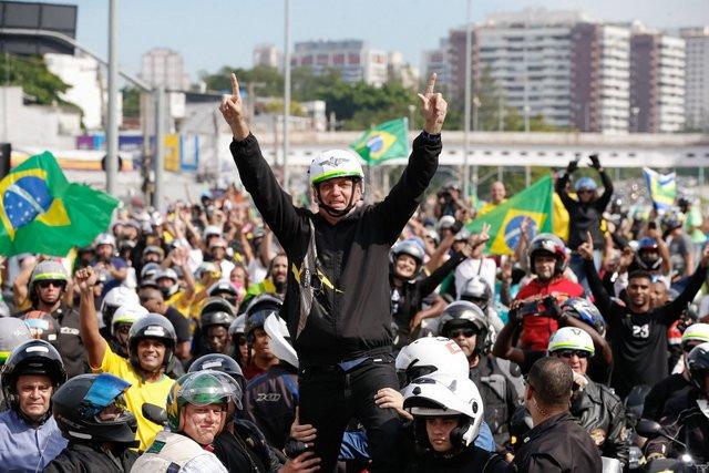 Un grupo de motoristas rodea al presidente brasileño, Jair Bolsonaro, el 23 de mayo, en Río de Janeiro, en una manifestación a su favor, en que destaca que todos están sin marcarillas y sin mantener ninguna distancia de seguridad. Foto: Alan Santos/PR